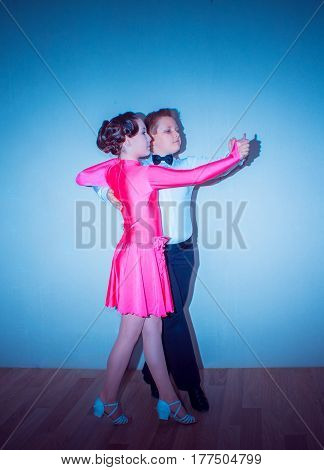 The young boy and girl posing at dance studio on gray. The ballroom dancing concept