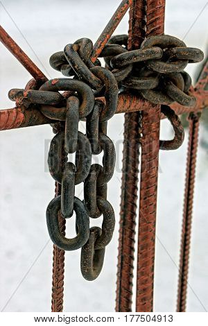 Iron, rusty chain on the gate with a steel rod