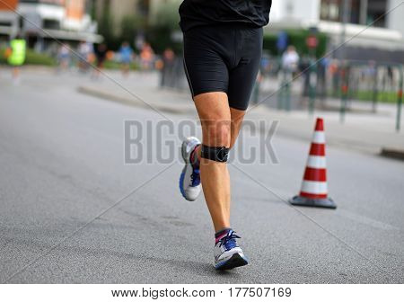 Athlete Running With Bandage On His Knees During The Marathon