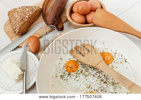 Fried Eggs in the Frying Pan,Breakfast Ingredients.Bread,Butter.Kitchen Accessories.Cooking.White Table.Selective FocusFood Background