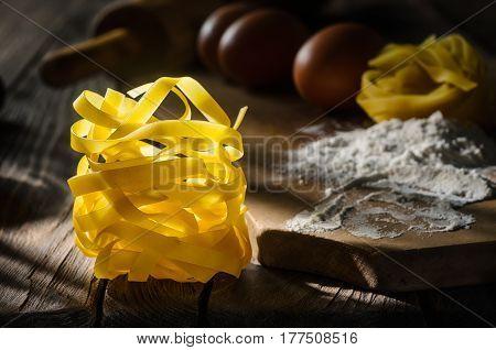 Raw Italian pasta tagliatelle on wooden table