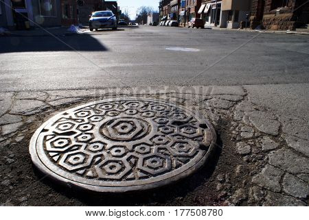 Street view of a closed manhole looking out on the intersection abroad in the downtown setting.
