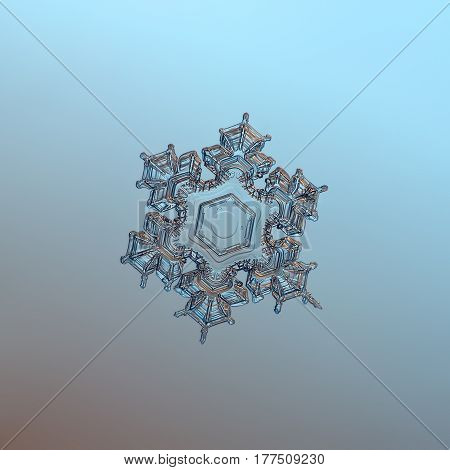 Macro photo of real snowflake: medium size snow crystal of star plate type with six short, spiky arms, and big, flat central hexagon with very simple inner pattern. Snowflake glitters on smooth gradient blue - brown background.