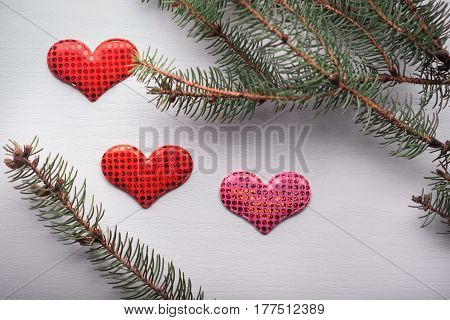 Wooden White Background With A Branch Of Pine And Three Hearts.