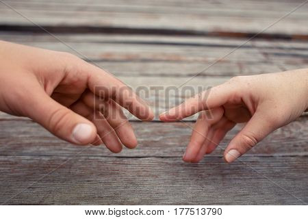 Hands stretching towards each other on wooden background