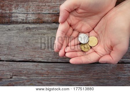 coins in the cupped palms on wooden background