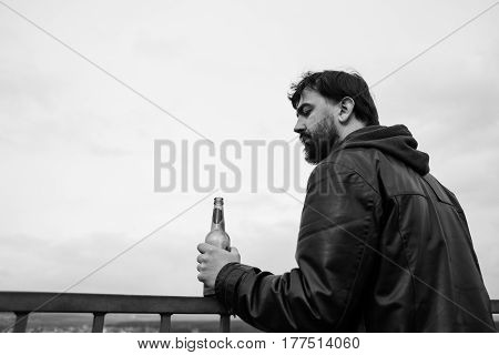 lonely adult bearded man alcoholic holds bottle of beer