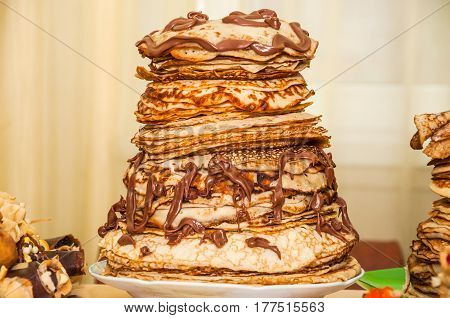 A big stack of pancakes decorated with boiled condensed milk while celebrating Russian Shrovetide (pancake week)