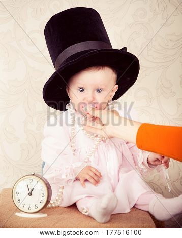The Baby Around The Clock On A Background