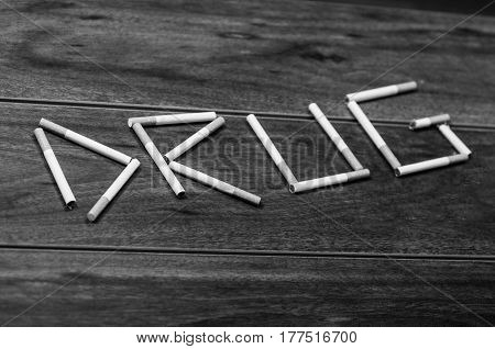 Cigarettes lying on wooden surface shaped into the word drug, artistic anti smoking concept, black and white edition.