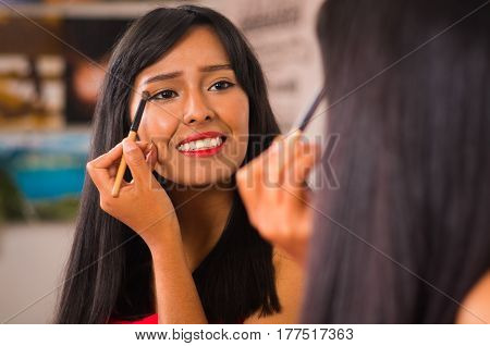 Beautiful brunette applying make up while smiling happily, seen from behind and face reflecting in mirror.