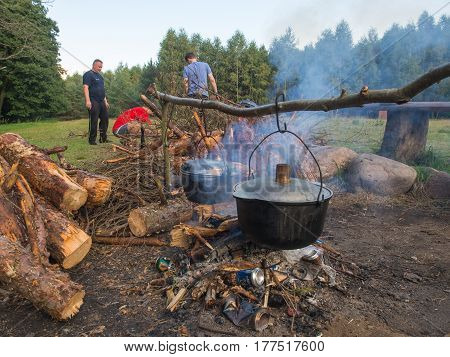 Cooking a meal on a campfire in metal vessels during a canoeing excursion