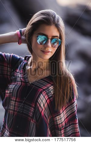 Outdoor fashion image of stylish young lady, fashionable.Lifestyle portrait of stunning hipster girl, wearing elegant glamour shirt dress and vintage sunglasses.