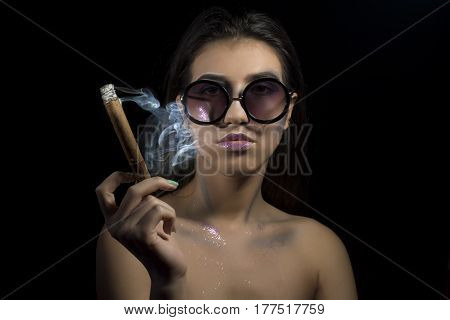 Young girl with make up and glasses smoking a cigar