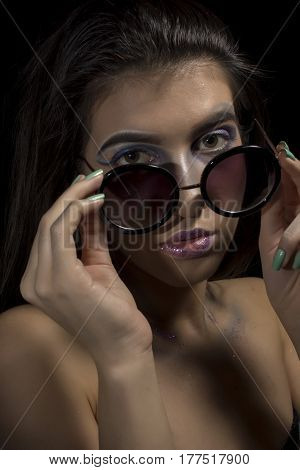 Portrait of a young girl with artistic make up and glasses