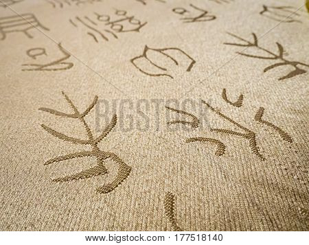 Piece of fabric decoratively weaved with Chinese characters using an ancient calligraphic style or form.