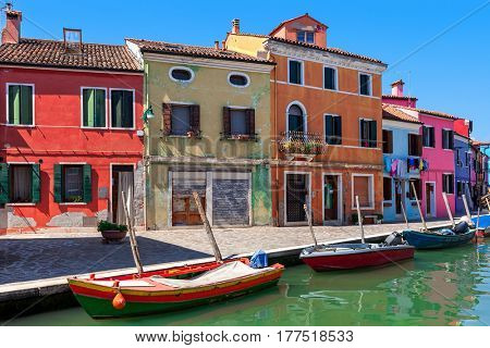 Old colorful houses along small canal with boats in Burano, Italy.