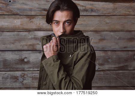 Handsome man wearing green jaket and torn jeans in wooden rural house interior. Processed with VSCO k2 preset