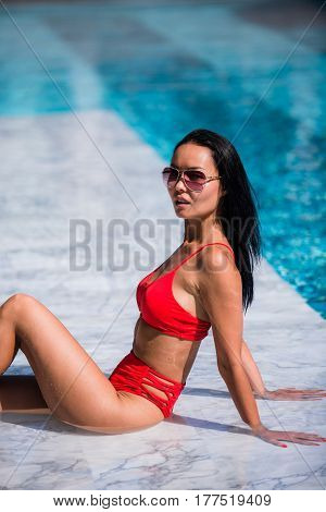 Sexy woman laying and relaxed near pool at cool black fashionable sunglasses, bra bikini pans, tan glowing skin woman, amazing hairstyle, long hair style.