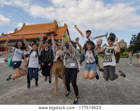 Taipei Taiwan - October 02 2016: Taiwanese Youths and a white tourist jump for joy on the Liberty Square in Taipei
