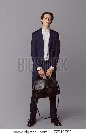 Business fashion man wearing blue suit with white shirt. Studio shot against grey. Holds the bag in hands. Processed with VSCO s3 preset