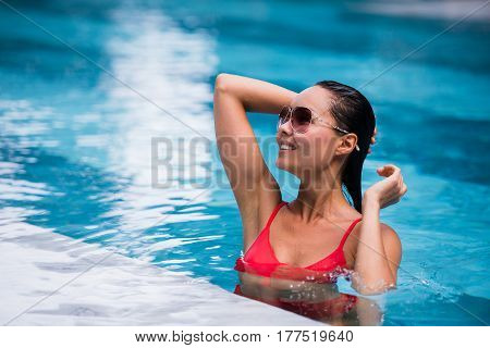 Woman wearing red swimsuit and sunglasses sitting in swimming pool, touching wet hair.