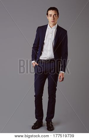 Business fashion man wearing blue suit with white shirt. Studio shot against grey. Processed with VSCO s3 preset