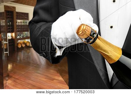 Closeup of a waiter opening a bottle of champagne with a wine cellar in the background..