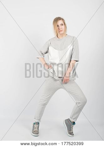 Young beautiful girl wearing grey clothes and sneakers posing isolated on white background