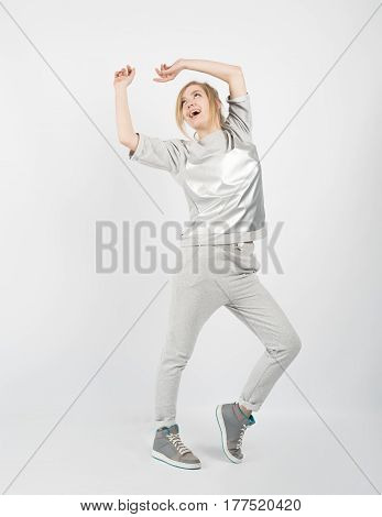 Young beautiful girl wearing grey clothes and sneakers posing isolated on white background. Hands up and looking up