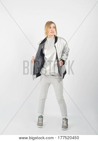 Young beautiful girl wearing grey clothes jacket and sneakers posing isolated on white background