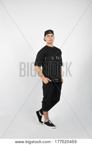 Young muscular man wearing black clothes and sneakers and snapback isolated on white background
