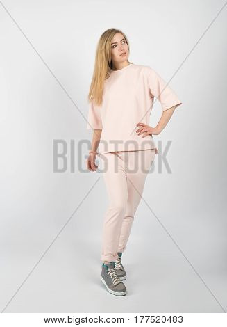 Young beautiful girl wearing pink clothes and sneakers posing isolated on white background