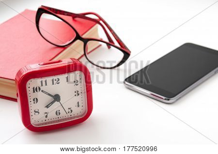 The Red Book, Glasses, Alarm Clock And Black Smartphone