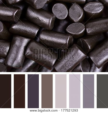 A background of cut pieces of black liquorice in a colour palette with complimentary colour swatches