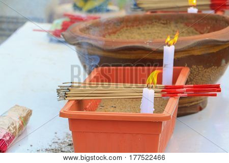 white candle and Incense in the pot