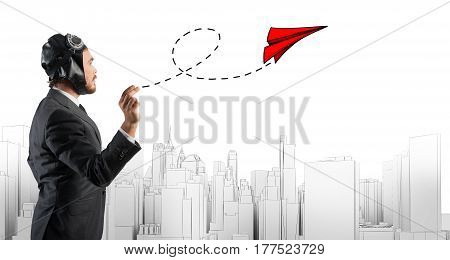 Businessman holding a small paper plane on cityscape background . Startup working enterprise concept