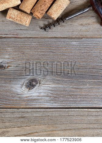 Overhead view of a top border of partial wine corks and vintage corkscrew on rustic wood