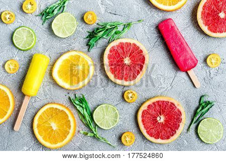 homemade citrus popsicles with fresh fruit slices on stone table background top view pattern