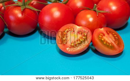 fresh ripe cherry tomatoes on blue background free space