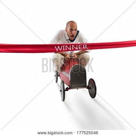 Businessman drives a toy car beyond the red ribbon at the arrival of a race