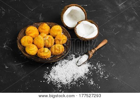 Coconut dessert biscuits (cookies) on a wooden plate. Ingredients for cookies (biscuits) fresh chopped coconut and coconut chips. Dark black concrete table background. Copy space.