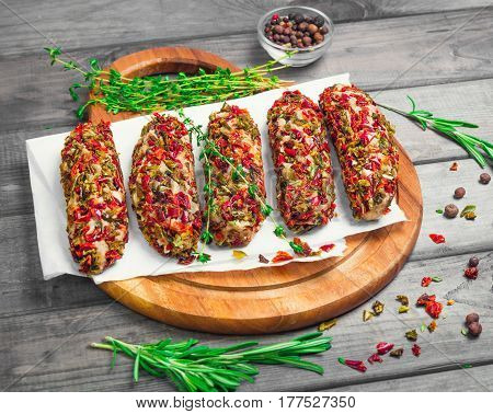 Not cooked meat lula kebab cutlets with vegetable breaded. Not cooked meat lula kebab cutlets with vegetable breaded peppers and tomatoes. Seasonings for meat lula kebab cutlets rosemary thyme and pepper Dried vegetables. Gray rustic wooden background.