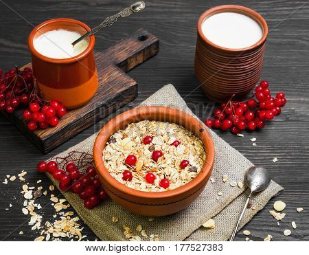 Morning meal breakfast. Cereal muesli with fruits and red berries. Yogurt for muesli and milk in ceramic ware. Dark brown wood background rustic style.