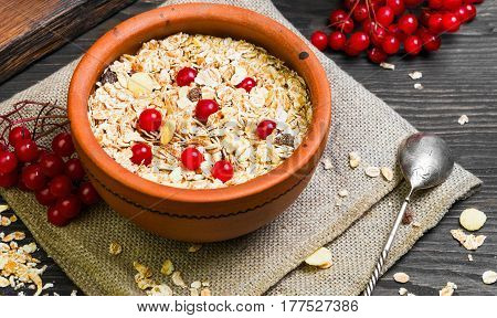 Morning meal breakfast. Cereal muesli with fruits and red berries. Ceramic bowl. Dark brown wood background rustic style.