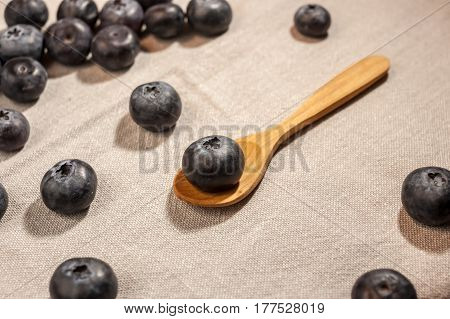 big blueberry in small wooden spoon on textile background