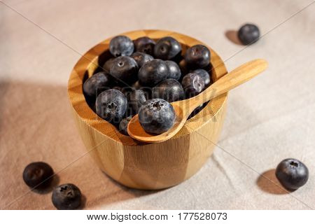 big blueberry in small wooden bowl on textile background