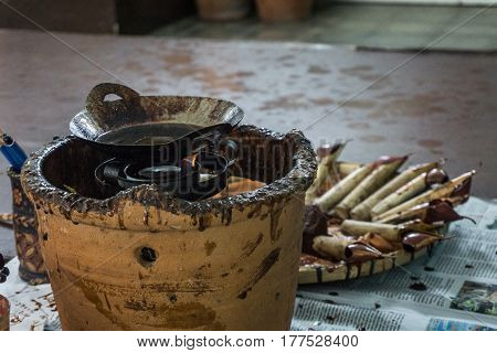 Canting and hot wax on top of wood table for Batik processing photo taken in Pekalongan Indonesia java