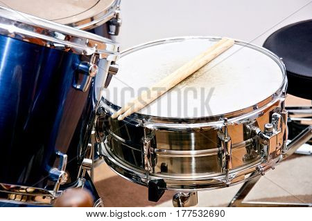 Drums conceptual image. Drumsticks lying on snare drum.