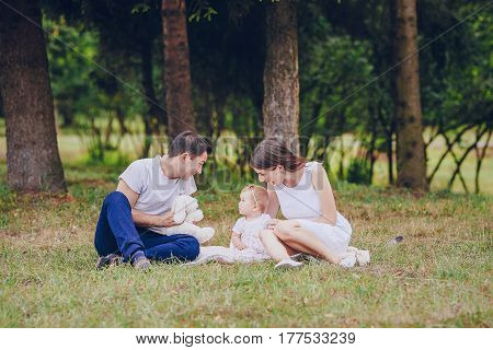 mom dad and little daughter sitting in a park on the grass and playing with toys